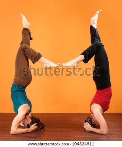 Two women in a coordinated yoga posture over orange background