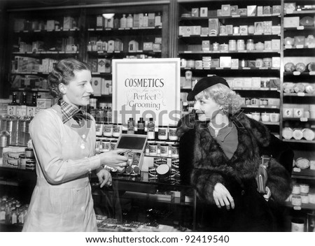 Two women in a drug store looking at each other - stock photo