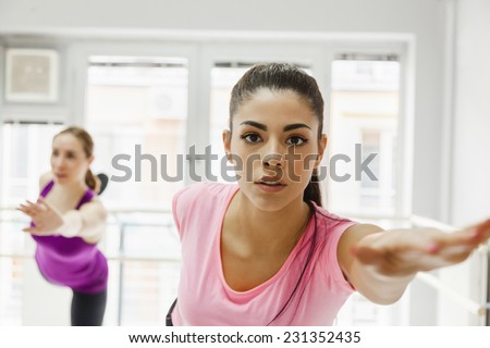 Two Women In A Gym Warming Up With Gymnastics And Stretching Exercises - stock photo