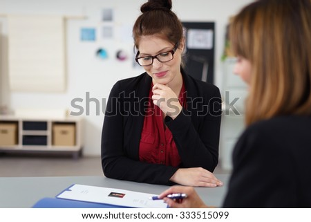 two women in a job interview sitting at the desk looking at a curriculum vitae - stock photo