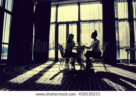 Two women in a large office, talking at the table, silhouettes.