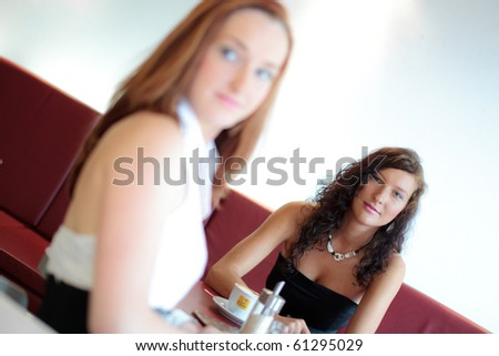 Two women in a restaurant, looking on a unseen arrival - stock photo