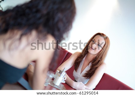 Two women in a restaurant, tilted version - stock photo