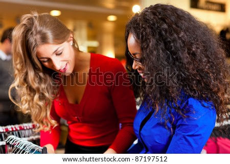 Two women in a shopping mall downtown looking for clothes