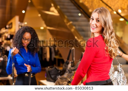 Two women in a shopping mall with Christmas decoration - stock photo