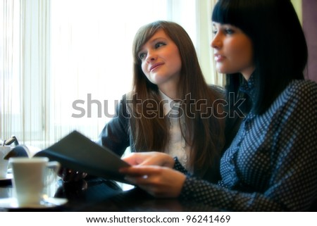 two women in cafe reading menu - stock photo