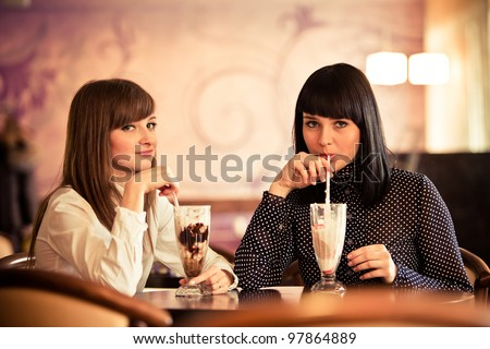 two women in caffe with cocktails - stock photo