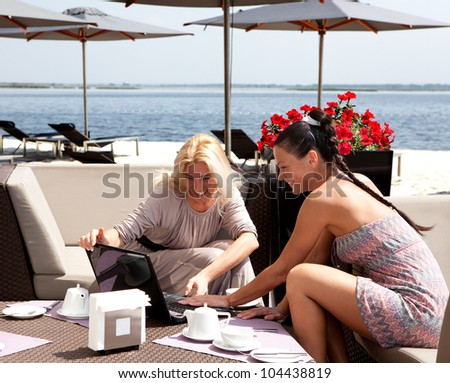 Two women in coffee look in netbook and smile - stock photo