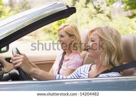 Two women in convertible car smiling - stock photo