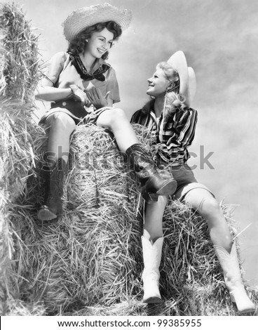 Two women in cowboy hats sitting on a haystack - stock photo