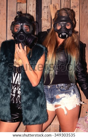 Two women in front of a wooden wall with gasmasks. - stock photo