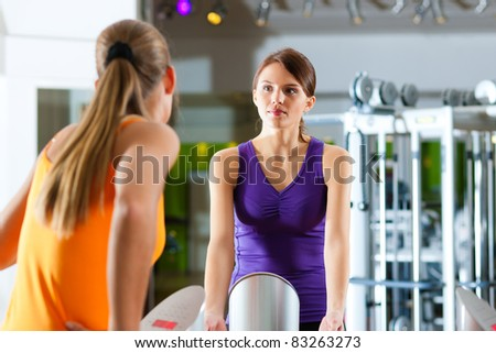 Two women in gym in front of a exercising machine - stock photo