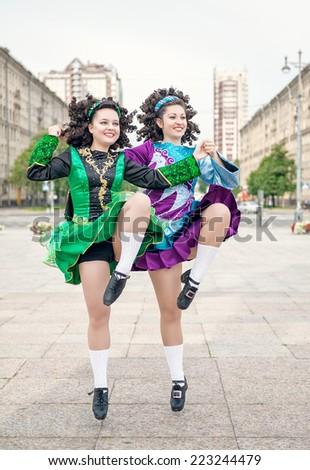 Two women in irish dance dresses dancing - stock photo