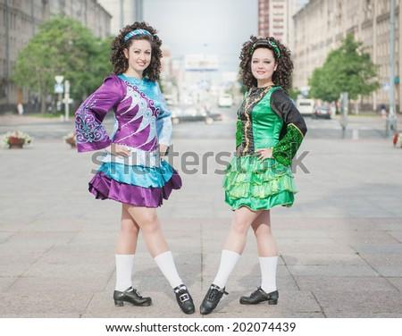 Two women in irish dance dresses outdoor - stock photo