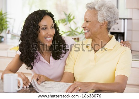 Two women in kitchen with newspaper and coffee smiling - stock photo