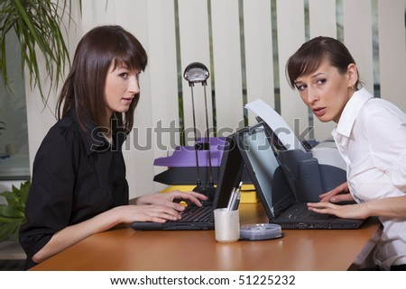 two women in office looking at someone - stock photo