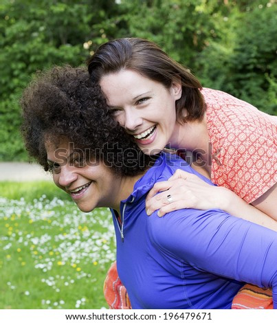two women in park hugging and laughing - stock photo