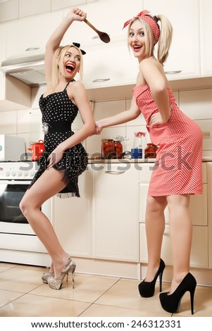Two women in pin up style. Women chefs cooking in the kitchen. - stock photo