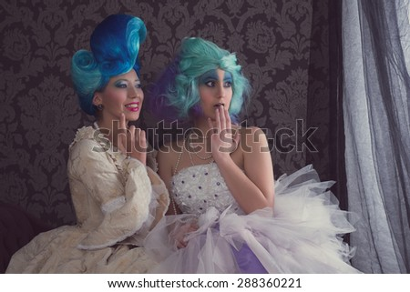 Two women in prom or historical dresses - stock photo
