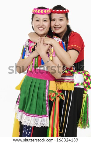 Two women in traditional dress embracing and smiling standing on white background