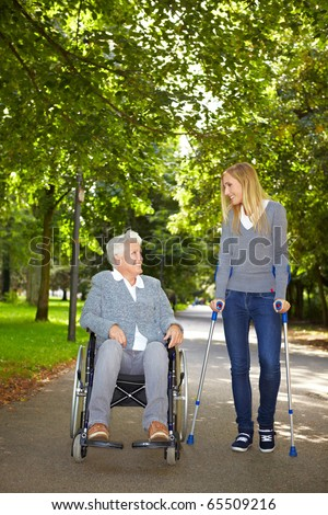 Two women in wheelchair and on crutches talking in a park - stock photo