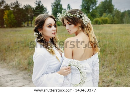 Two women in white dresses with flowers outdoors