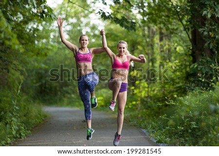 Two women jumping together - stock photo