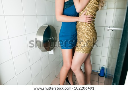 Two women kissing in the toilet of a club or disco - stock photo