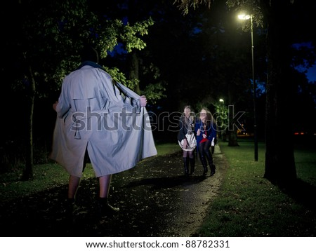 Two women laughing at a Flasher at night in the park - stock photo