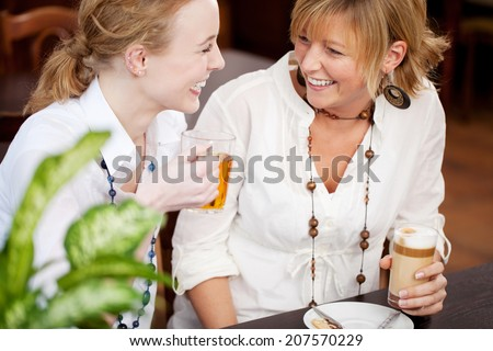Two women laughing in a restaurant as they sit together at a table enjoying a glass of tea and coffee together - stock photo