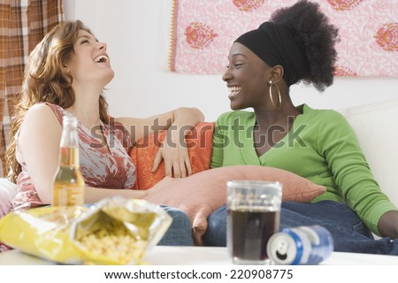 Two women laughing on sofa - stock photo