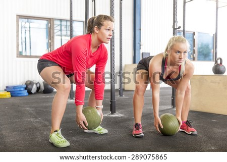Two women lifts slam balls at the gym - stock photo