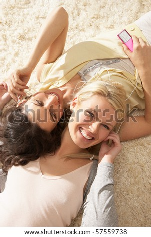 Two Women Listening To MP3 Player On Headphones Together Relaxing Laying On Rug At Home - stock photo