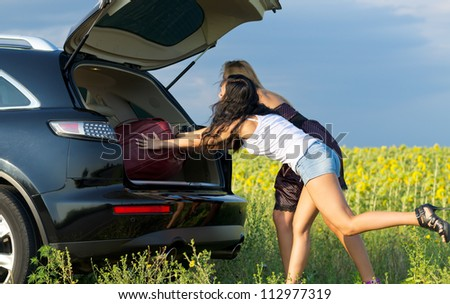 Two women loading luggage into the back of an estate vehicle parked alongside the road in the countryside near a field of sunflowers - stock photo