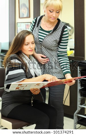 Two women look catalog of hair colors near mirror in beauty salon