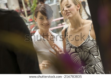 Two women looking at a display window of a store. - stock photo