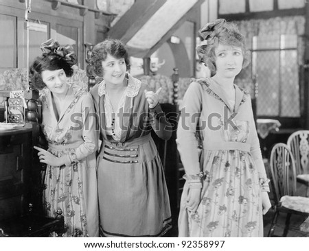 Two women looking at a third woman - stock photo