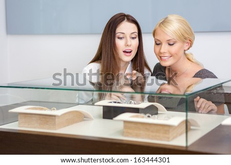 Two women looking at showcase with jewelry at jeweler's shop. Concept of wealth and luxurious life - stock photo