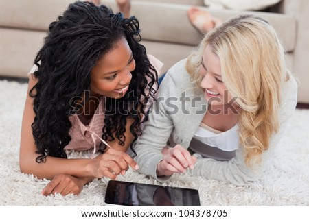 Two women lying down on the floor are looking at each other with a tablet in front of them - stock photo