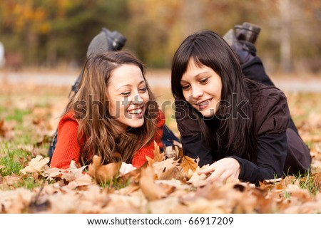 Two women lying in the autumn park leaves - stock photo