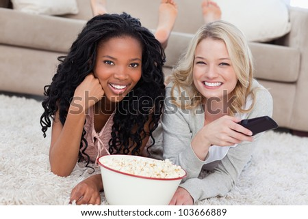 Two women lying on the ground with popcorn are smiling at the camera and have a TV remote - stock photo