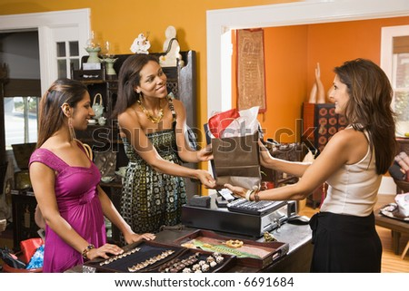Two women making purchase  from sales clerk in boutique. - stock photo