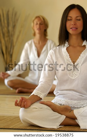 two women meditating - stock photo