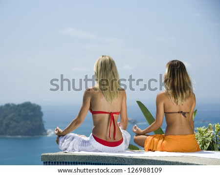 Two women meditating by infinity pool - stock photo