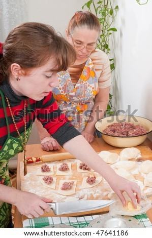 Two women mould pies with a meat stuffing. - stock photo