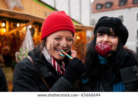Two women on Christmas market eating apple and candy in front of a booth, it is cold - stock photo
