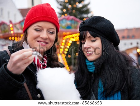 Two women on Christmas market eating cotton candy in front of a booth, it is cold