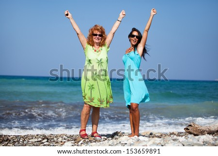 Two women on the beach holding their hands up