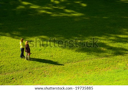 Two women on the bright grass - stock photo