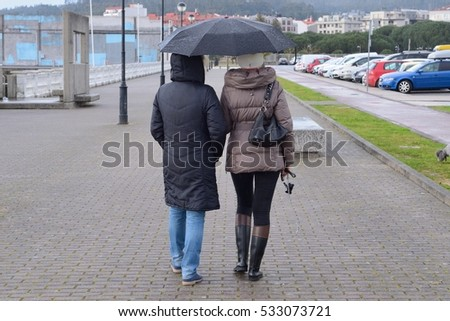 two women on the street with umbrellas in the rain